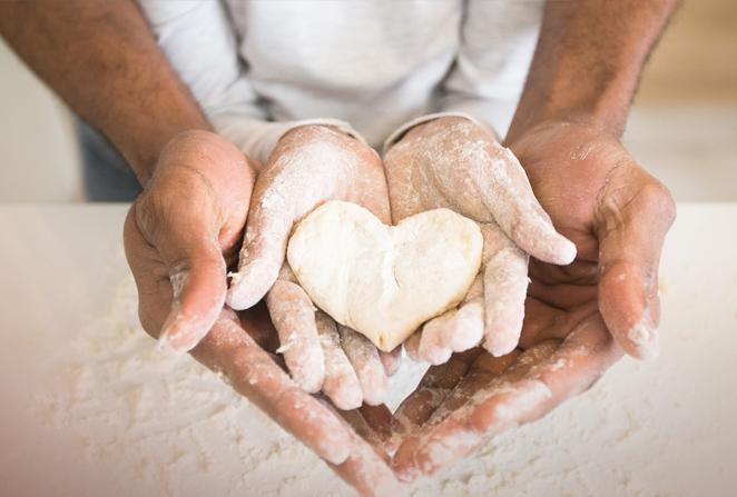 Zwei Hände halten ein Herz aus Teig.